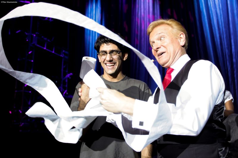 "Magician Jeff Hobson, also known as ""The Trickster"" begins his famous paper trick by swirling a toilet paper roll around. An audience member standing by watches with a big grin on his face."