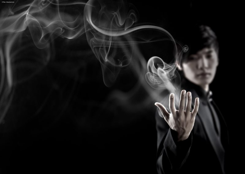 "The magician known as ""The Manipulator"" extends his open hand. Smoke billows from his open palm."