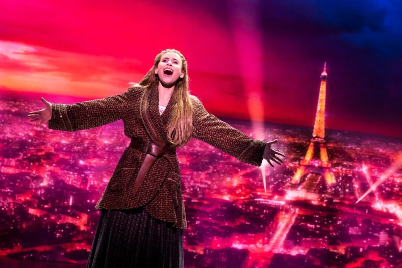 Anastasia sings her heart out with the Eiffel Tower in the background.