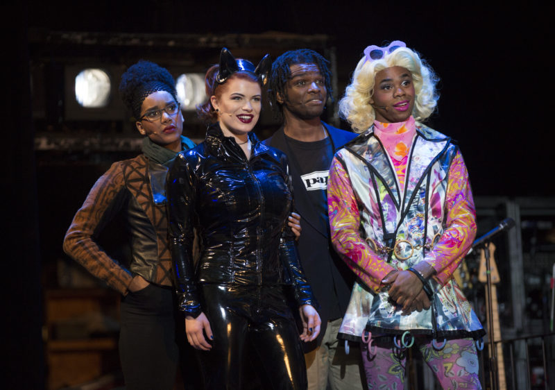 Maureen, dressed in a leather catsuit, Joanne, dressed in normal attire, Angel, dressed in drag, and Collins, dressed in a tee shirt and jeans, look on.