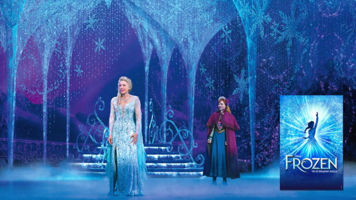 A blond woman in a light blue gown (Elsa) stands in an ice palace with her back turned to a red headed woman dressed in nordic winter attire (Anna)